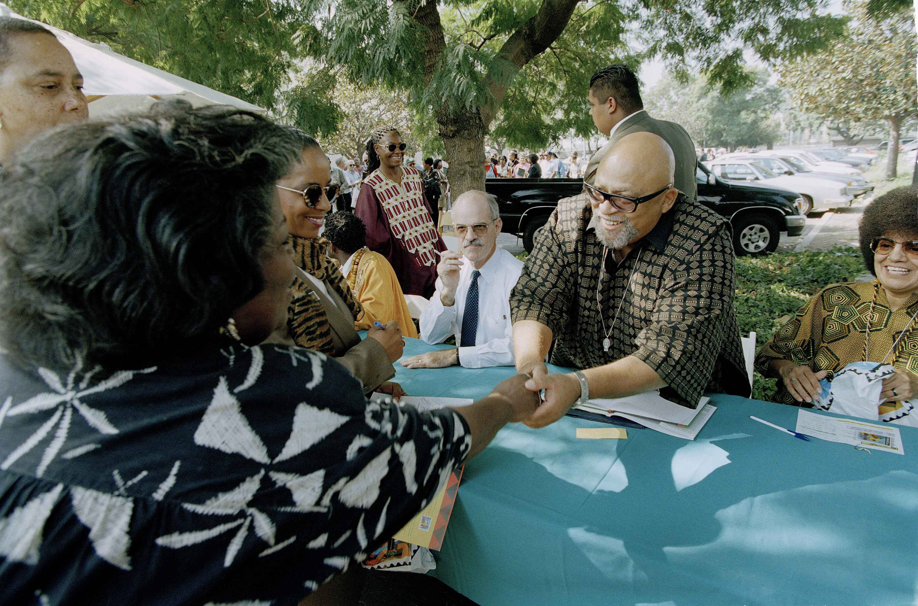 """Dr. Maulana Karenga, left, greets well-wishers during the """"First Day of Issuance"""" dedication ceremony for the U.S. Postal Service's first-ever Kwanzaa stamp, in Los Angeles, Oct. 22, 1997. The stamp, designed by artist Syntia Saint James, commemorates the popular African American festival of family, community and culture, created by Dr. Karenga. (AP Photo/Reed Saxon)"""